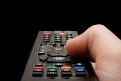 Remote control. Television remote control being held and operated against a balck background Royalty Free Stock Photos