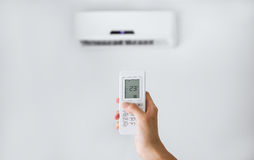 Remote control for air conditioner on a white wall. Royalty Free Stock Image