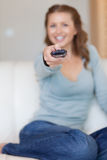 Remote control being used by young woman Stock Photo