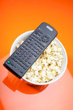 Remote control and bowl with pop corn Royalty Free Stock Images