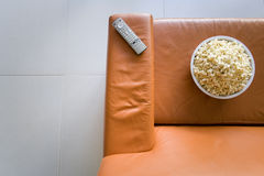 Remote control and bowl of popcorn on orange sofa, elevated view stock photography