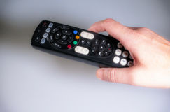 Remote Control. Detail photo of a hand operating a tv remote control Stock Photos