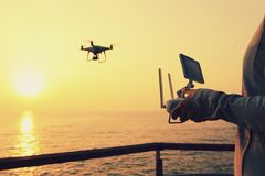Remote control a flying drone which taking photo over sunrise sea Royalty Free Stock Image
