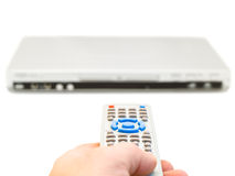 Remote control in hand. And dvd player over the white background stock photo