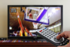 Remote control in the hand, during a basket match, sports Stock Photos