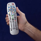 Remote Control In Hand With Blue Background Stock Photography