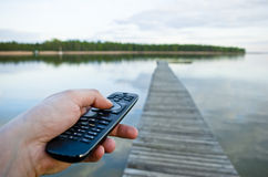 Remote control in hand and natural landscape Stock Photo
