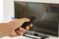 Remote control in hand to enjoy with television Royalty Free Stock Photos