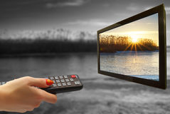 Remote control in hand and TV royalty free stock photography