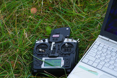 Remote control and laptop are on the green grass Stock Images