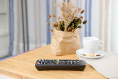 The remote control is placed on a wooden table Royalty Free Stock Images