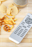 Remote control and salty snack Stock Photos