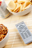 Remote control and salty snack Stock Images
