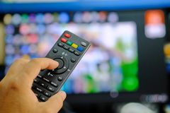 Remote control satellite receiver in hand blurred background. Royalty Free Stock Photo