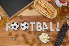 Remote control, slate, snacks, drinks and football word arranged on table. Overhead of remote control, slate, snacks, drinks and football word arranged on table Stock Images