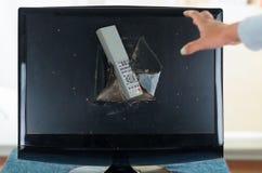 Remote control stuck inside broken computer screen Stock Image