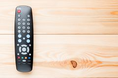Remote control for switching channels on the TV set. On the wooden floor on the right Stock Photography