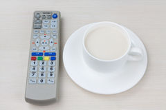 Remote control and tea. A remote control and a cup of tea on the table Stock Photography