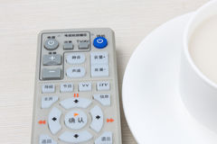 Remote control and tea. A remote control and a cup of tea on the table Stock Photos