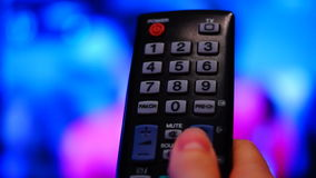 Remote control. Thumb touching the channel button on a remote stock footage