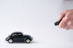 Remote control of toy black car model. Hand of man holding and push remote control of toy black car model on white background with copy space.Technology Royalty Free Stock Images