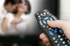 Remote control and tv. Hand holding remote control pointing the TV stock image