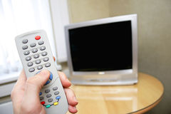 Remote control and tv. Human hand holding remote control against tv Stock Image