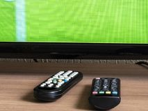 Remote control and tv. Remote control and television with a soccer field on the screen stock photos