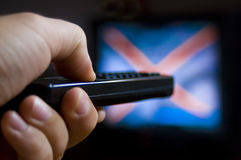 Remote control for watching TV. The tv remote control in the hand searches through the canal stock photo