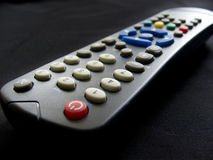 Remote controler. Black remote controler with red on/off button in strong - left bottom point. Isolated on dark background Royalty Free Stock Image