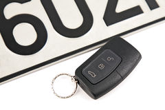 Remote controlled car key and registration plate. Remote controlled car key and a part of registration plate on a white background Royalty Free Stock Photos