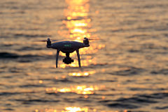 Remote controlled drone flying sparkle sunlight on sea. KAGAWA, JAPAN - JUNE 8, 2017: Remote controlled drone Dji Phantom4Pro equipped with high resolution video Royalty Free Stock Photos