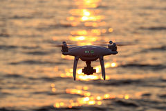 Remote controlled drone flying sparkle sunlight on sea. KAGAWA, JAPAN - JUNE 8, 2017: Remote controlled drone Dji Phantom4Pro equipped with high resolution video Stock Image