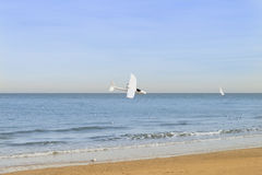 Remote-controlled plane flying in the sky, above the sea Royalty Free Stock Photo