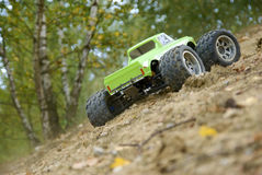 Remote controlled rc monster car. Green RC monster truck riding uphill outdoors stock image