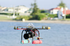 Remote-controlled surveillance helicopter. With eight rotors flying over water carrying camera royalty free stock image