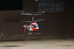 Remote controlled toy helicopter in flight. Flying remote controlled helicopter rotating blades Royalty Free Stock Photos