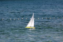 Remote controlled yellow sailing boat with clear white sails used as children toy in local bay on restless sea surrounded with. Protective net on warm sunny day royalty free stock photos