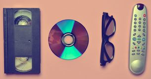 Remote controller, 3d glasses, CD, video cassette on a pink. Pastel background. Retro technology royalty free stock image