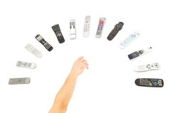 Remote Controls. A man's hand reaching for remote controls stock image