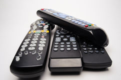 Remote Controls. A stack of television and DVD remote controls stacked on white.  It shows the confusion of choices Stock Photo