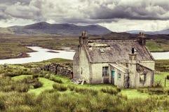 A remote cottage set against a mountainous Scottis stock photography