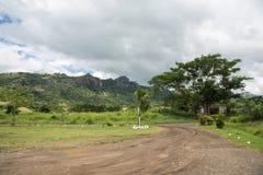 Remote Fiji. Mountain landscape with rainforest, plants, dirt road and cumulus clouds in Port Denarau, Fiji Stock Photos