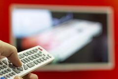 The remote in the hand switch channels on the TV hanging on the red wall Stock Image