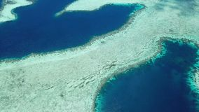 Aerial View of coral reef structure in Raja Ampat. The remote and healthy coral reefs found throughout Raja Ampat, Indonesia, are surrounded by calm seas. This stock footage