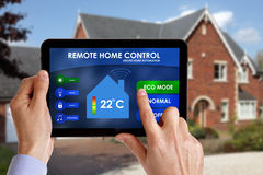 Remote home control. Holding a smart energy controller or remote home control online home automation system on a digital tablet. All screen graphics made up stock image