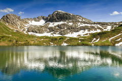 Remote lake up high in the alpine mountains. Schrecksee. Beautiful reflections in the remote Schrecksee lake up high in the alpine mountains spotted with snow Royalty Free Stock Image