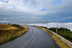 Remote mountain service road with clouds Stock Photos