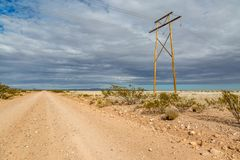 A Remote New Mexico Landscape. A dusty road and electricity pylons in rural New Mexico royalty free stock images