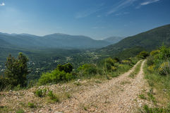 Remote rough cart track leading off into the mountains in Kefalo. Nia under a blue sky Royalty Free Stock Images